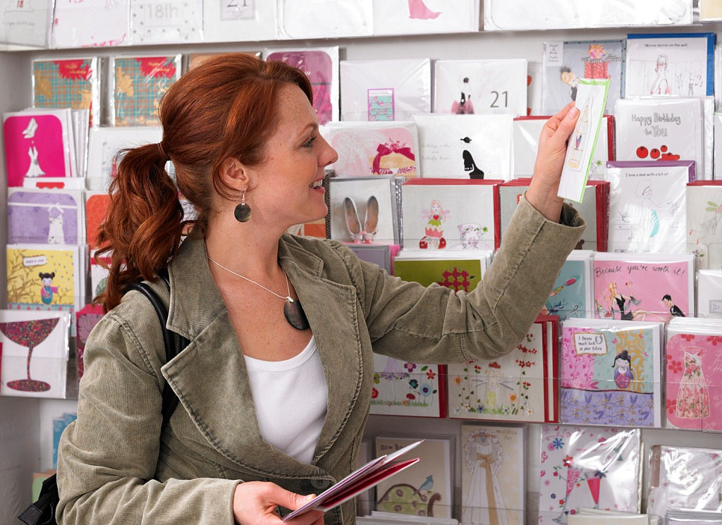 Young woman looking at greeting cards on rack